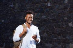Homem de sorriso com saco e telefone celular que está pela parede de pedra Imagens de Stock Royalty Free