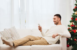 Homem de sorriso com smartphone em casa para o Natal Fotos de Stock