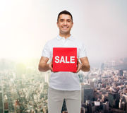 Homem de sorriso com suspiro da venda acima sobre o fundo da cidade Fotografia de Stock Royalty Free
