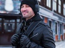Homem de sorriso com trouxa que anda na rua e que escuta a música através dos fones de ouvido Fotos de Stock Royalty Free
