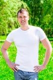 homem de sorriso de 35 anos em um t-shirt e em calças de brim Imagem de Stock Royalty Free