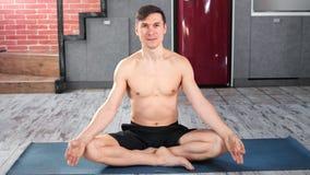 Homem de sorriso do iogue dos esportes que levanta o assento na posição de lótus que aprecia a meditação que olha a câmera filme