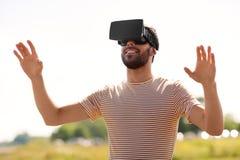 Homem de sorriso em auriculares da realidade virtual fora imagens de stock