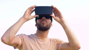 Homem de sorriso em auriculares da realidade virtual fora video estoque