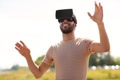 Homem de sorriso em auriculares da realidade virtual fora fotografia de stock royalty free