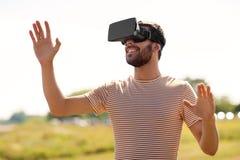 Homem de sorriso em auriculares da realidade virtual fora fotos de stock royalty free