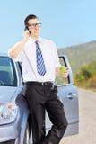 Homem de sorriso em seu café bebendo do automóvel e fala em um p Fotografia de Stock