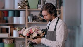Homem de sorriso feliz do florista que faz o grupo da forma no florista povos, negócio, venda e conceito floristry Ramalhete vídeos de arquivo