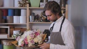 Homem de sorriso feliz do florista que faz o grupo da forma no florista povos, negócio, venda e conceito floristry Ramalhete filme