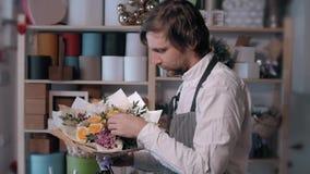 Homem de sorriso feliz do florista que faz o grupo no florista povos, negócio, venda e conceito floristry Ramalhete com rosas filme