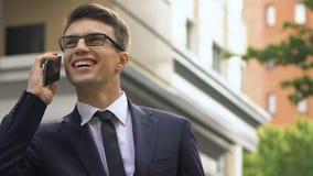 Homem de sorriso feliz no smartphone de fala do terno na rua da cidade, contrato rentável vídeos de arquivo