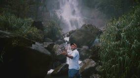 Homem de sorriso feliz novo do blogger do curso que toma o selfie do smartphone na cachoeira tropical majestosa épico da selva de vídeos de arquivo