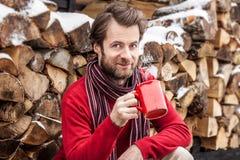 Homem de sorriso feliz que bebe o chá quente exterior - paisagem do campo do inverno Imagem de Stock Royalty Free