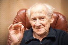 Homem de sorriso idoso que guarda uma tabuleta Imagens de Stock