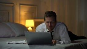 Homem de sorriso na camisa branca na cama que sorri e que conversa no portátil, caso de escritório vídeos de arquivo