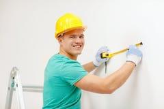 Homem de sorriso na parede de medição do capacete protetor Foto de Stock