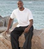 Homem de sorriso nas rochas Fotografia de Stock Royalty Free