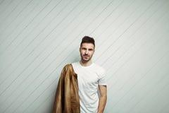 Homem de sorriso no casaco de cabedal vestindo no ombro, fundo de madeira branco do t-shirt vazio fotografia de stock