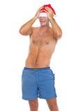 Homem de sorriso no short da praia que puxa o chapéu de Santa sobre os olhos fotografia de stock royalty free