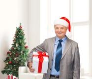 Homem de sorriso no terno e chapéu do ajudante de Santa com presente Fotografia de Stock