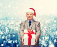 Homem de sorriso no terno e chapéu do ajudante de Santa com presente Imagens de Stock Royalty Free