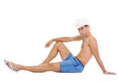 Homem de sorriso nos shorts e chapéu que senta-se no assoalho imagem de stock royalty free