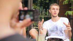 Homem de sorriso novo do moderno que fala na câmera Entrevista video da gravação de Vlogger 4K filme
