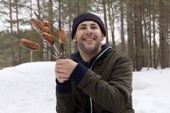 Homem de sorriso novo que guarda uma salsicha em um cuspe nas madeiras fotografia de stock
