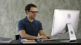 Homem de sorriso novo que senta-se em sua mesa no escritório e que trabalha no computador filme