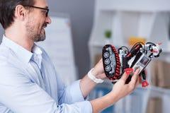 Homem de sorriso observando um robô novo do brinquedo fotografia de stock