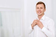Homem de sorriso que abotoa-se até a camisa do branco do pescoço Fotografia de Stock Royalty Free