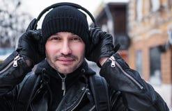 Homem de sorriso que anda na rua do inverno e que escuta a música através dos fones de ouvido Fotografia de Stock Royalty Free