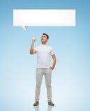Homem de sorriso que aponta o dedo até a bolha do texto Fotos de Stock Royalty Free