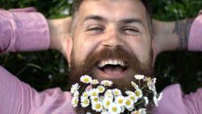 Homem de sorriso que aprecia o dia ensolarado morno no prado verde, conceito do frescor da mola Moderno feliz com as flores branc vídeos de arquivo