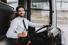 Homem de sorriso que conduz o ônibus de excursão Motorista profissional foto de stock royalty free