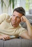 Homem de sorriso que encontra-se na televisão de observação do sofá Imagens de Stock