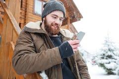 Homem de sorriso que está e que usa o smartphone fora no inverno Fotografia de Stock Royalty Free