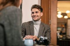 Homem de sorriso que fala com a mulher no café fotografia de stock