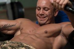 Homem de sorriso que faz Excerise abdominal Foto de Stock Royalty Free