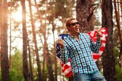 Homem de sorriso que guarda a bandeira dos EUA Comemorando o Dia da Independência de América 4 de julho Homem que tem o divertime Imagens de Stock Royalty Free