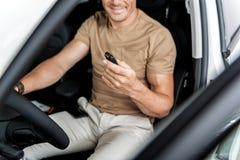 Homem de sorriso que guarda equipamentos eletrônicos no braço Foto de Stock