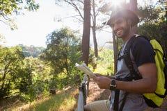 Homem de sorriso que guarda o mapa e a posição perto da cerca Foto de Stock Royalty Free