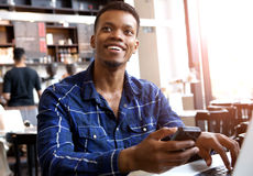 Homem de sorriso que guarda o telefone celular com o portátil no café imagens de stock