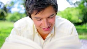 Homem de sorriso que lê uma novela interessante video estoque