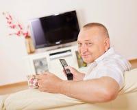 Homem de sorriso que presta atenção à tevê Imagem de Stock Royalty Free