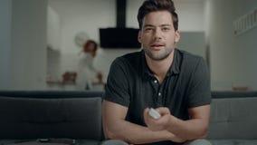 Homem de sorriso que procura o programa da tevê na cozinha Homem relaxado que verifica os canais de televisão vídeos de arquivo