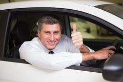 Homem de sorriso que senta-se em seu carro que dá os polegares acima imagem de stock royalty free