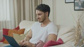 Homem de sorriso que trabalha com o sofá do laptop em casa Homem novo que conversa em linha filme