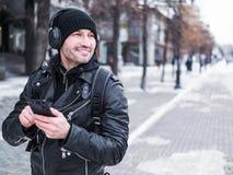 Homem de sorriso que usa a aplicação da música em seu smartphone Inverno Fotos de Stock Royalty Free