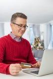 Homem de sorriso que usa o cartão e o portátil de crédito para comprar em linha em casa durante o Natal Imagens de Stock